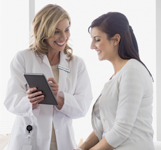 Female healthcare provider talking with woman in exam room