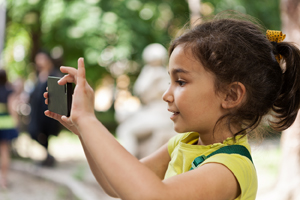 Girl taking a photo with a smart phone.