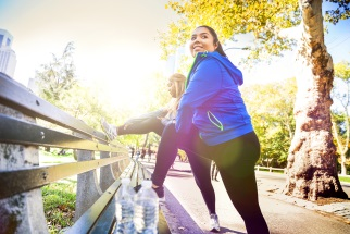 Two people in exercise clothing stretching on a park bench