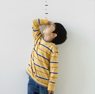 Toddler measuring himself with a drawn ruler on a wall.