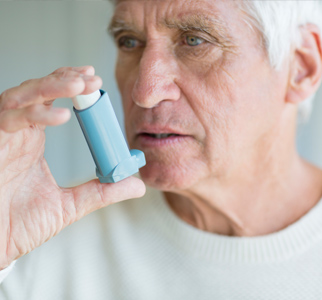 Older man preparing to use an inhaler